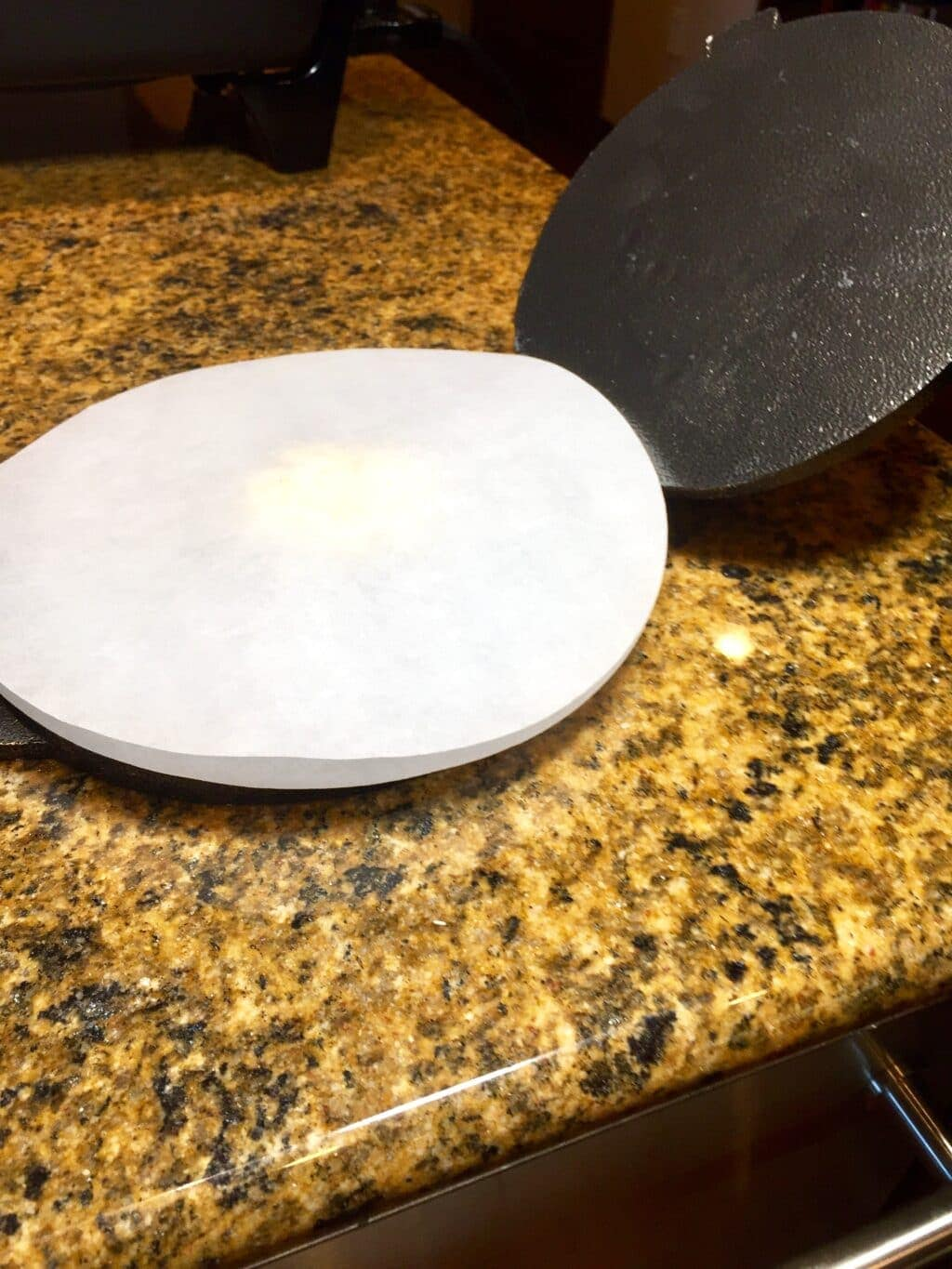 Masa dough between 2 sheets of parchment in a tortilla press