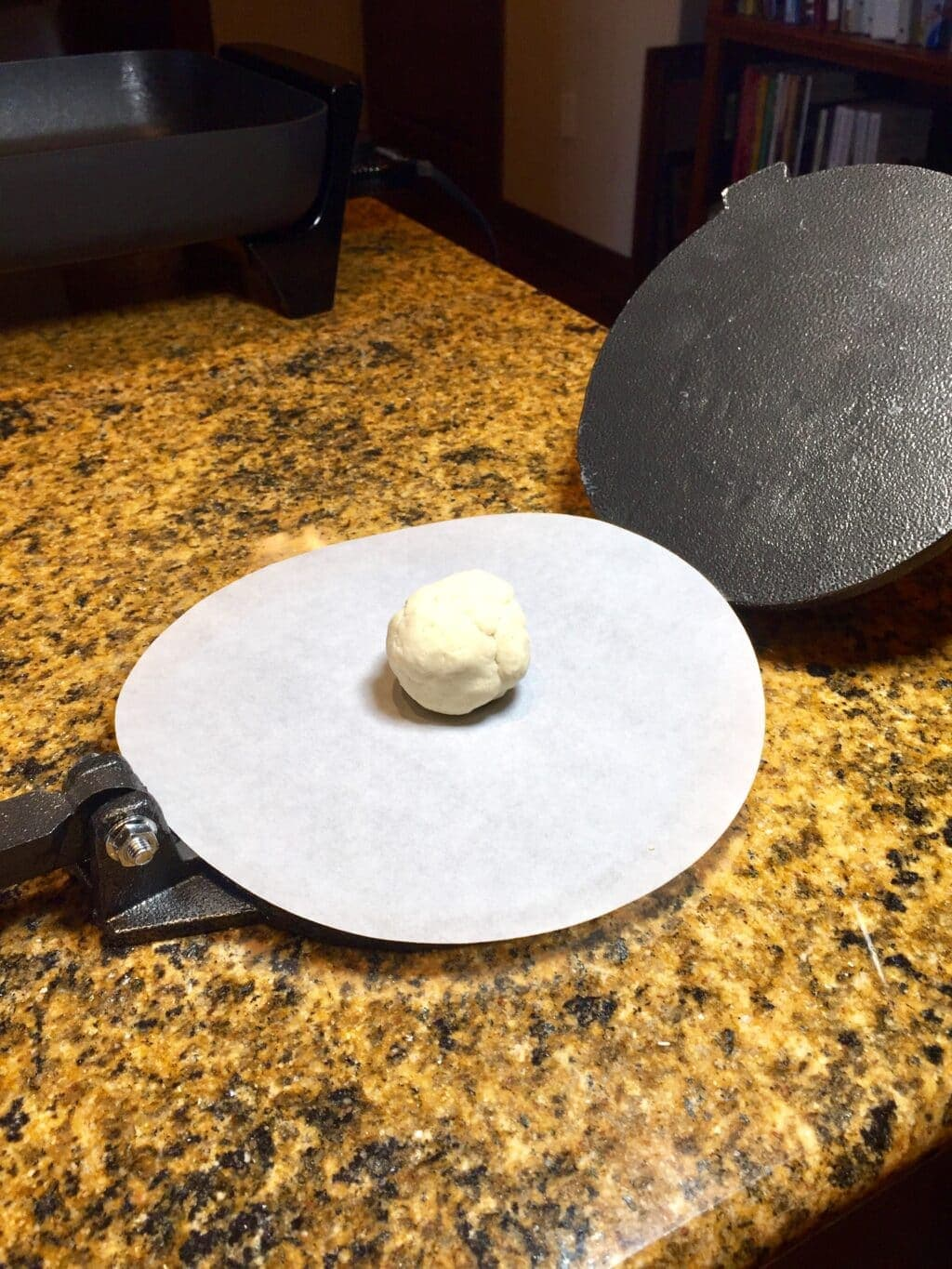 Masa ball on a sheet of parchment in a tortilla press