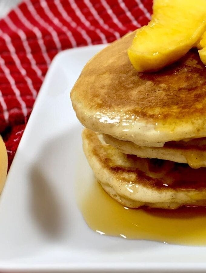 Peach Cobbler Pancakes with dripping syrup on a white plate