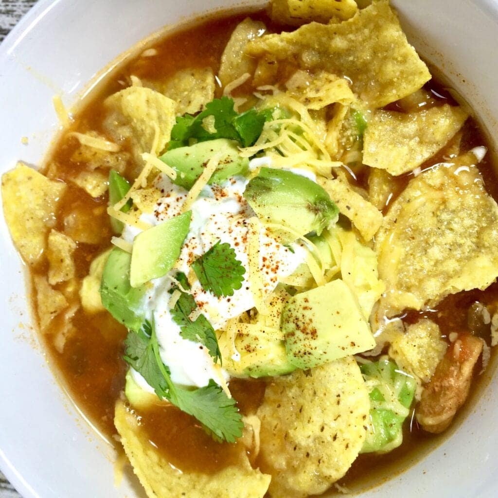Tortilla soup with avocados in a white bowl