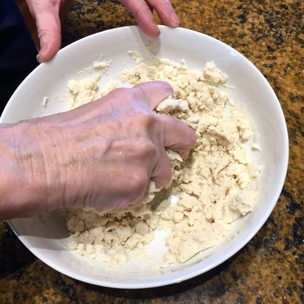 Hand mixing masa and water in a white bowl