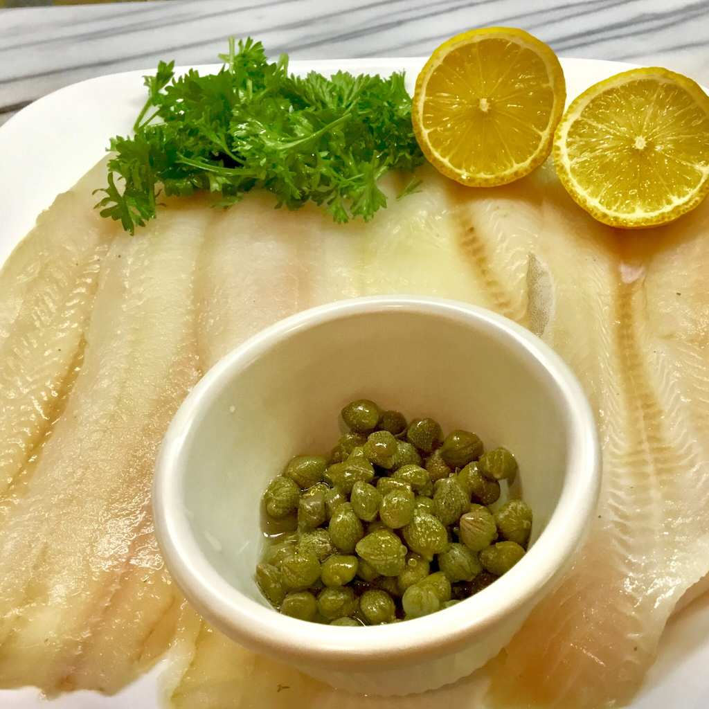 Dover sole fillet with capers, parsley and lemon on a white plate