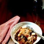 Julia's Easy Coq au Vin in a white dish with a red napkin and a glass of wine
