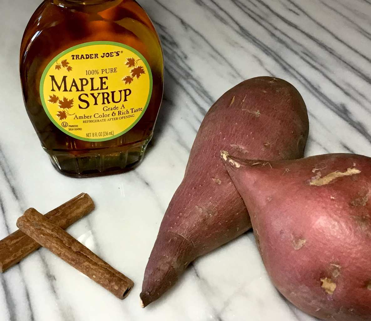 Sweet potatoes. Maple syrup and cinnamon sticks on a marble top