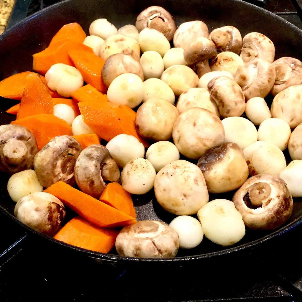 Mushrooms, carrots and onions frying in a pan