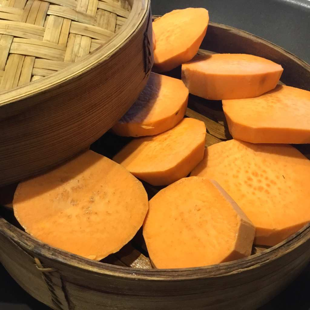Sliced sweet potatoes in a bamboo steamer