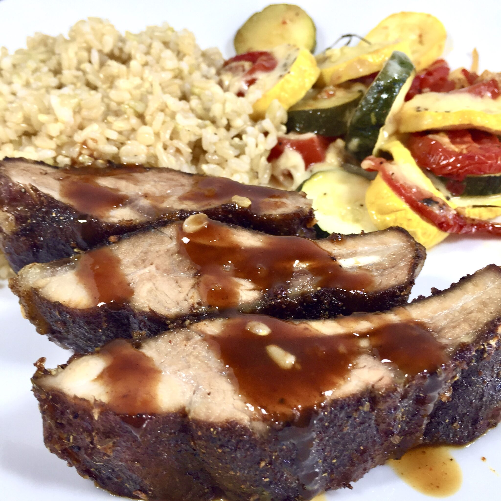 Oven Smoked Dry Ribs with rice and vegetables on a white plate