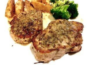 Juicy pork chops, broccoli and sautéed apples on a white plate